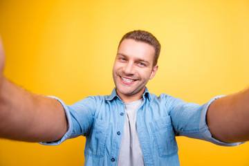 Self portrait of attractive, cute, smiling man with bristle, stubble in jeans shirt, shooting selfie with two hands on front camera over yellow background