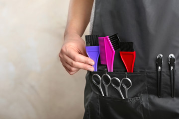 Woman in black apron with professional hairdresser set on light background, closeup