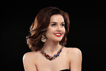 Beautiful woman with elegant jewelry on black background