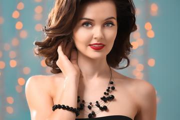 Beautiful woman with elegant jewelry against defocused lights