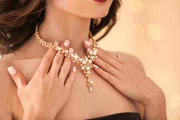 Beautiful woman with elegant jewelry on light background, closeup