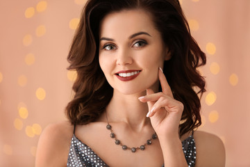 Beautiful woman with elegant jewelry on light background