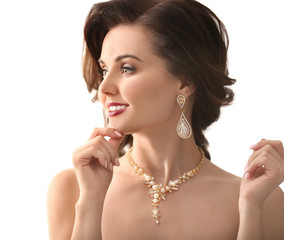 Beautiful woman with elegant jewelry on white background