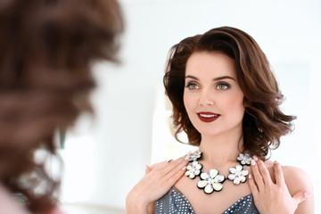 Beautiful woman with elegant jewelry near mirror