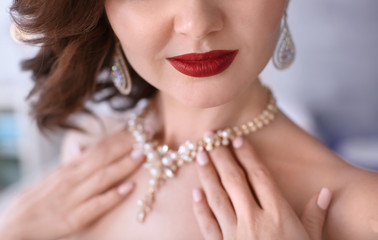 Beautiful woman with elegant jewelry on blurred background, closeup