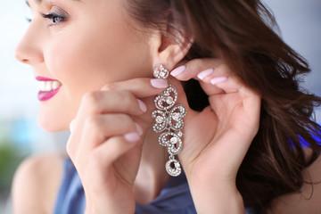 Beautiful woman putting on elegant earrings, closeup