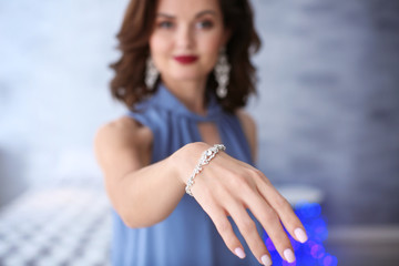 Young woman showing her beautiful bracelet indoors