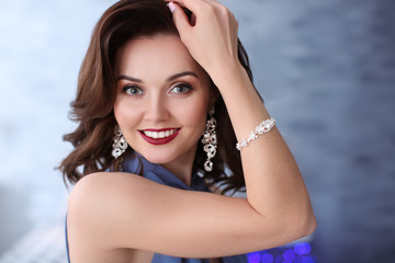 Beautiful woman with elegant jewelry indoors