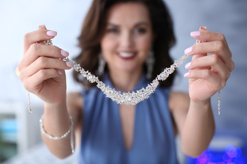 Young woman showing her beautiful necklace indoors