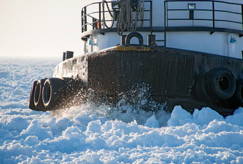 closeup of tugboat hull cutting through thick ice in Lake Michigan