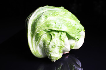 Iceberg lettuce salad. Whole green iceberg lettuce salad on black reflective studio background. Isolated black shiny mirror mirrored background for every concept.
