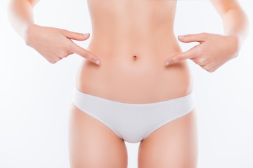 Menstruation ovulation depilation epilation laser liposuction sport weight loss concept. Cropped close up photo of skinny woman's ideal belly demonstrating with fingers isolated on white background