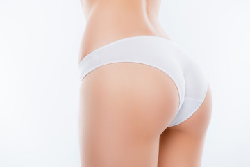 Photo sur Plexiglas Ane Cropped close up half-turned photo of ideal elastic flawless beautiful woman's ass wearing white underlinen underclothes isolated on background, having confidence with sanitary napkin, towel