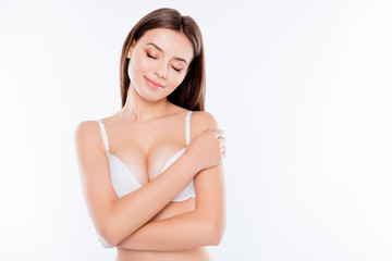 Close up portrait of charming beautiful attractive sexy nude woman with no-make-up closed eyes showing her big breast isolated on white background copy-space