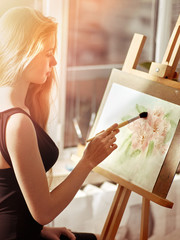 Artist watercolor painting on easel in studio. Girl paints with brush in morning sunlight dawn light toning. Indoor home interior for handmade crafts with window background.