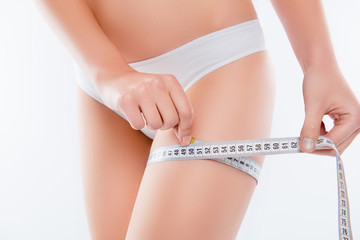 Nutrition eating vitality wellness concept. Cropped close up photo of woman's hands holding centimeter and measuring the size of thin slender skinny leg wearing white underlinen isolated on background