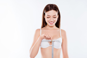 Portrait of excited satisfied joyful beautiful nude woman taking measures of her breast using centimeter wearing white bra isolated on background, wellbeing, wellness, perfection concept
