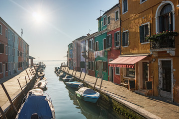 Empty street with a water channel on the Burano island near Venice on a sunny day