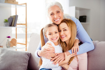 Close up portrait of excited cheerful comfort sweet friendly touching supporting cute beautiful with blonde hair ponytails schoolgirl beautiful mom charming granny hugging her family members