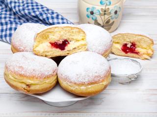 Tradycyjne Polskie pączki z cukrem pudrem i dżemem serwowane w Tłusty Czwartek.