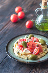 Pasta with tomato sauce, olives and capers on the plate