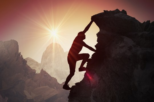 Silhouette of young man climbing on mountain.