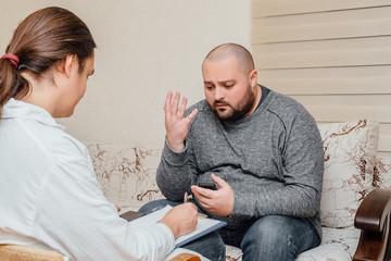 Depressive fat man talking with psychologist. Psychologist writes notes