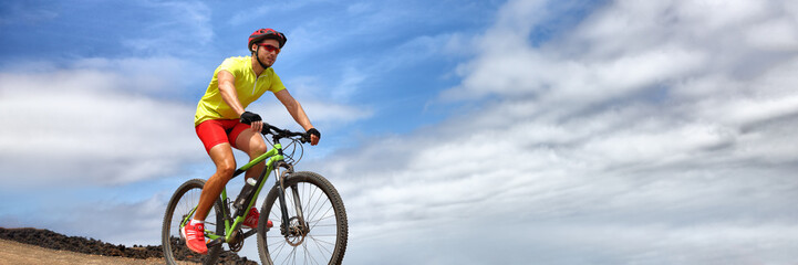 Sport athlete fitness training biking on mountain MTB bike landscape banner panorama. Copy space on blue sky background. Man cyclist riding bicycle outdoors.