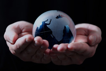Hand holding translucent globe with blue background.