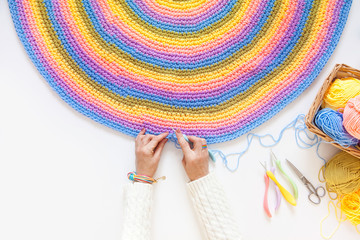 Colorful round yarn mat. Yarn in coils and tangles. A woman knits crocheted.