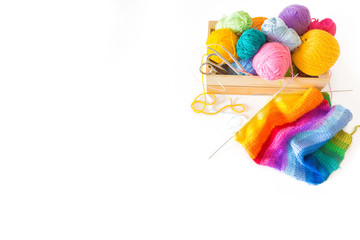 Colored yarn in the balls of a wooden box. Knitting needles and crochet hooks. Scissors. Isolate. White background.