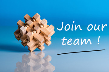 Job recruiting advertisement represented by 'JOIN OUR TEAM' texts on blue background with wooden brain teaser talking about the difficult tasks, new challenges and opportunities