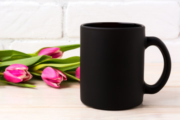 Black coffee mug mockup with magenta pink tulips bouquet