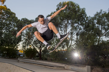 man practicing radical skate board jumping and enjoying tricks and stunts in concrete half pipe skating track in sport and healthy lifestyle