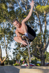 young American man in naked torso practicing radical skate board jumping and enjoying tricks and stunts in concrete half pipe skating track