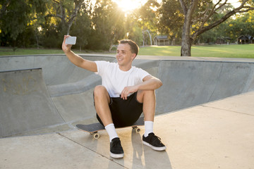 man 30s sitting on skate board after sport boarding training session taking selfie photograph portrait or picture on mobile phone
