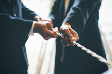 Business Cooperation Concept. Image of business team pulling a rope as an element of the success teamwork.