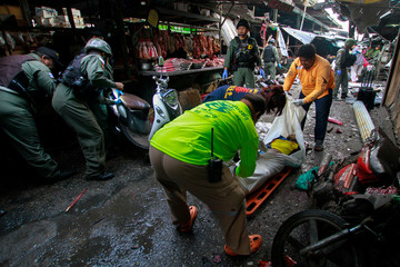 Rescue workers prepare to carry a dead body out of the site of a bomb attack in Yala