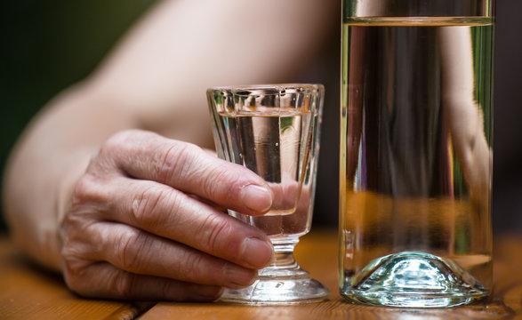 eine Frau sitzt an einem Tisch und trinkt Alkohol