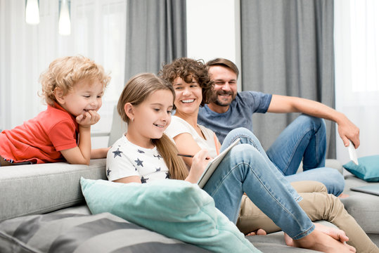 Joyful family of four gathered together in cozy living room and enjoying each others company, pretty little girl drawing picture with pencil