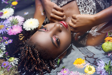 African woman with bright make up lies in the water with flowers close-up upside-down