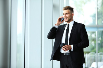 Young businessman standing in an office near the window and talking on a cell phone.