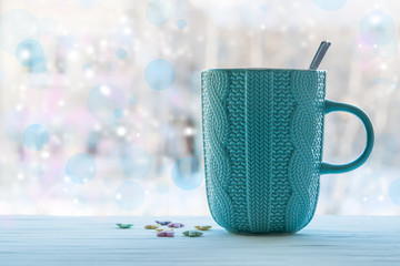 A hot Cup of tea on a wooden table against the background blur of the window on a winter day, Christmas homemade holidays background