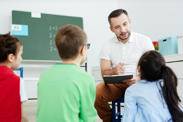 Contemporary teacher pointing at one of kids while listening to their answers
