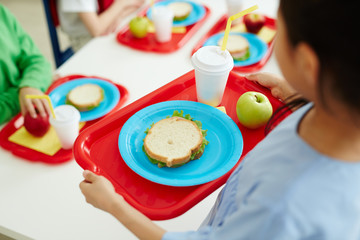 Schoolgirl carrying red plastic tray with sandwich on plate, glass of drink and green apple during lunch break