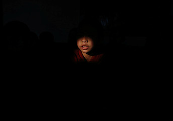 Light illuminates a novice monk as he offers prayers at the premises of a Saraswati temple during the Shreepanchami festival dedicated to goddess of education Saraswati in belief that the goddess will help devotees excel in education, in Kathmandu