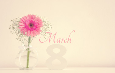 Image of International women day concept with beautiful flower in the vase on wooden table.