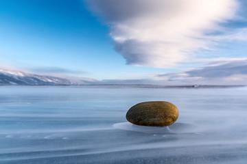 Stone on the ice of Lake Baikal