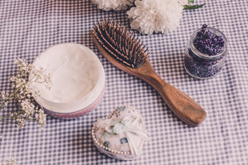 Natural spa set for woman. Hair care, pampering. Sandalwood comb, cream, sleeping mask. Flat lay photography, top view, wooden background