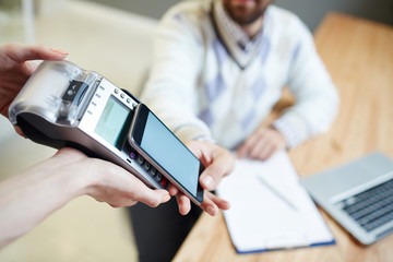 Contemporary client with smartphone using system of contactless payment